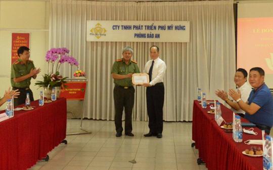 Đại diện Công ty TNHH Phát triển Phú Mỹ Hưng nhận bằng khen từ Thượng tá Lê Văn Lâm – Phó Trưởng Công an Quận 7